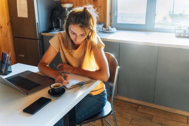 Piękna młoda kobieta siedzi przy biurku, studiując lub pracuje na nowoczesnym laptopie w domu w kuchni