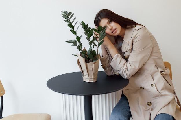 Piękna młoda kobieta siedzi przy stole i uśmiecha się
