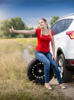 Piękna młoda kobieta siedzi przy zepsutym samochodzie i jedzie autostopem