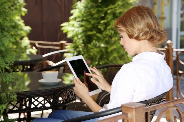Piękna młoda kobieta siedzi w kawiarni