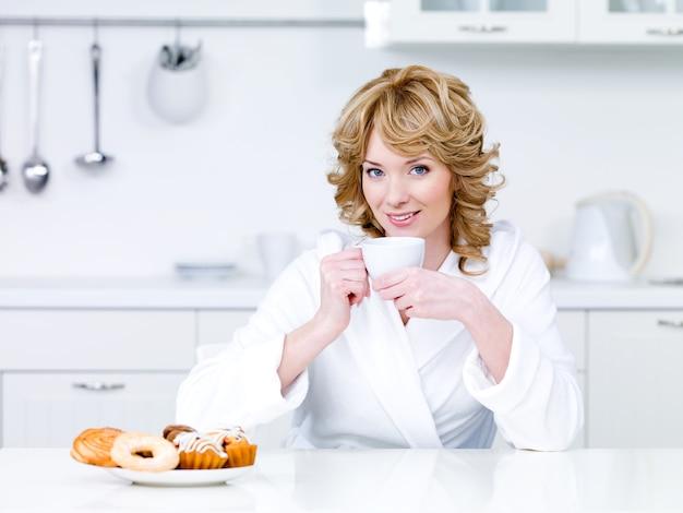 Piękna młoda kobieta siedzi w kuchni i picia kawy - w pomieszczeniu