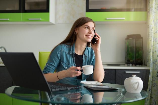 Piękna młoda kobieta siedzi w kuchni przy stole z laptopem, picie herbaty i rozmawia przez telefon