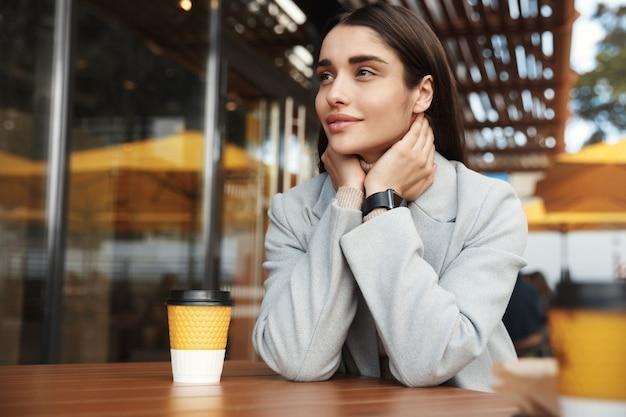 Piękna młoda kobieta siedzi w płaszczu i smartwatch czeka w kawiarni.