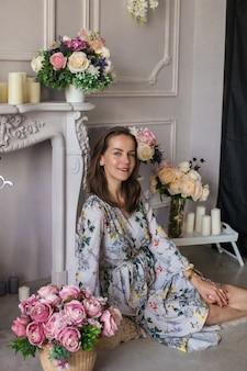 Piękna młoda kobieta siedzi w pokoju wśród kwiatów