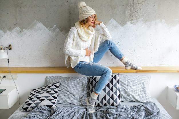 Piękna młoda kobieta siedzi w sypialni przed ścianą na sobie biały sweter