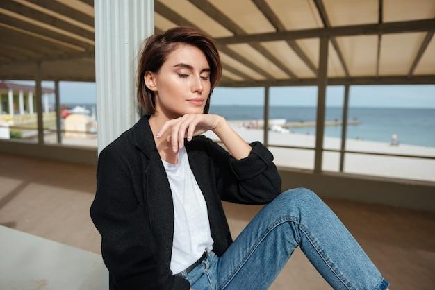 Piękna młoda kobieta siedzi z zamkniętymi oczami i relaksując się na werandzie w pobliżu morza