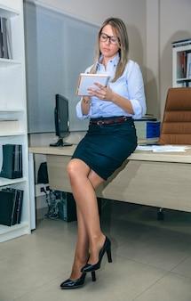 Piękna młoda kobieta siedzi ze skrzyżowanymi nogami i pisze notatki w miejscu pracy