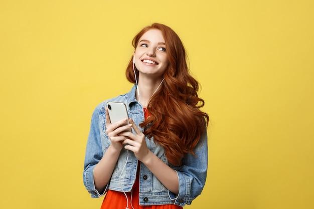 Piękna młoda kobieta słucha muzyka na jasnożółtym tle w hełmofonach