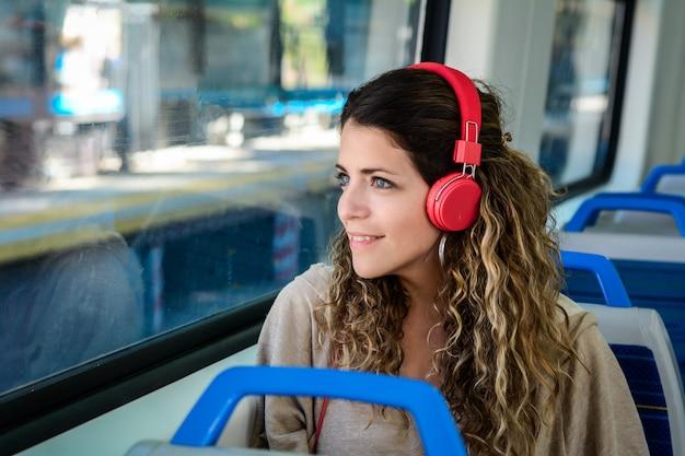 Piękna młoda kobieta słucha muzyka w pociągu