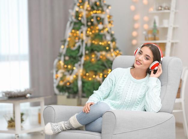 Piękna młoda kobieta słucha muzyki w salonie urządzonym na boże narodzenie