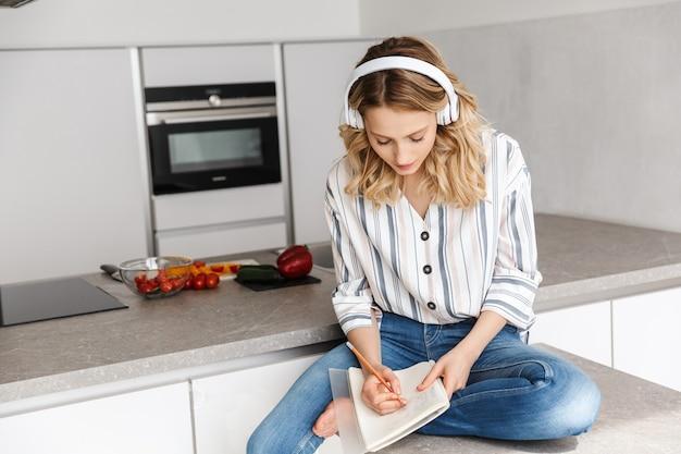 Piękna młoda kobieta słucha muzyki w słuchawkach, siedzi w kuchni i robi notatki