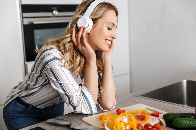 Piękna młoda kobieta słucha muzyki w słuchawkach w kuchni, robi świeżą sałatkę