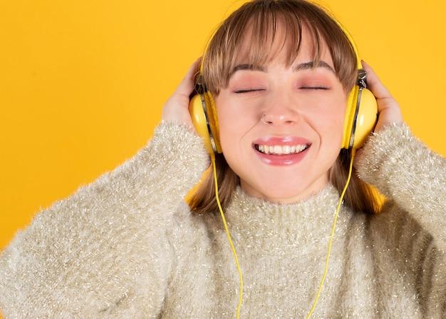 Piękna młoda kobieta słucha muzyki w słuchawkach z zamkniętymi oczami, żółte tło
