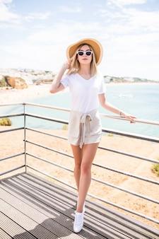Piękna młoda kobieta spaceru po mieście z widokiem na ocean