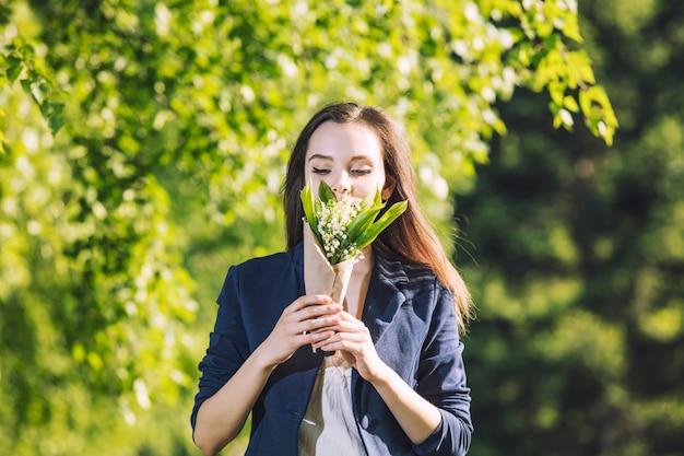 Piękna młoda kobieta spaceru po parku z bukietem konwalii w rękach portretu