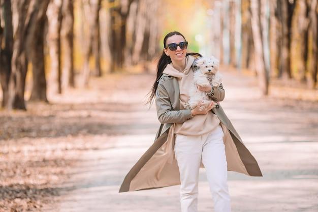 Piękna młoda kobieta spaceru z białym szczeniakiem