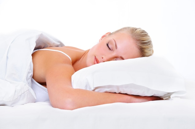 Piękna młoda kobieta śpi i widząc słodkie sny