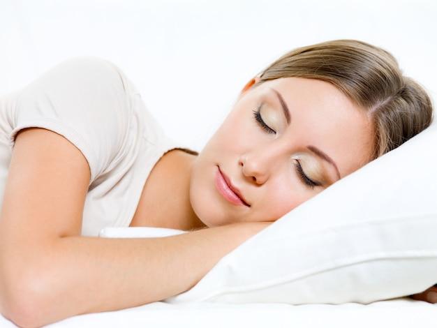 Piękna młoda kobieta śpi na kanapie w domu