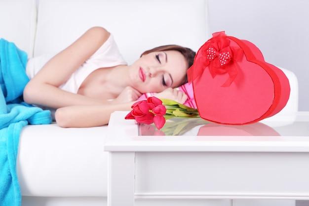 Piękna młoda kobieta śpi na kanapie w pobliżu stołu z prezentami i kwiatami, z bliska