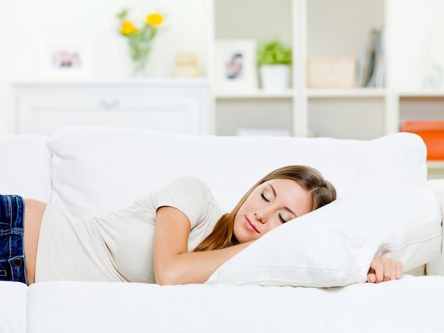 Piękna młoda kobieta śpi na łóżku w sypialni w domu