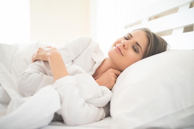Piękna młoda kobieta śpi w łóżku