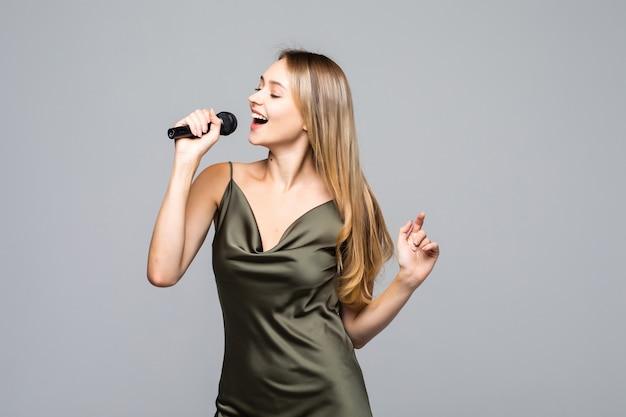 Piękna młoda kobieta śpiewa do mikrofonu na szarej ścianie