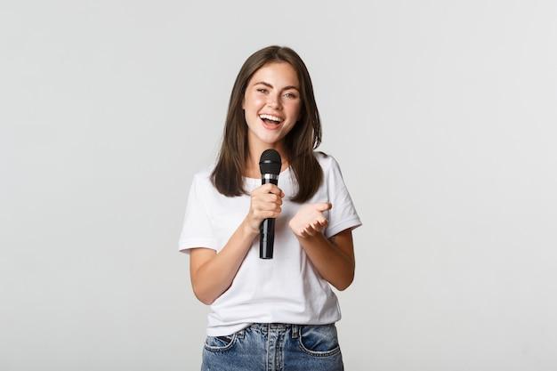 Piękna młoda kobieta śpiewa piosenkę do mikrofonu na karaoke, stojąc na biało.
