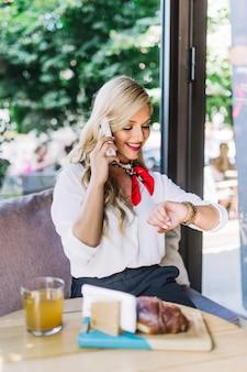 Piękna młoda kobieta sprawdza czas podczas gdy opowiadający na telefonie komórkowym