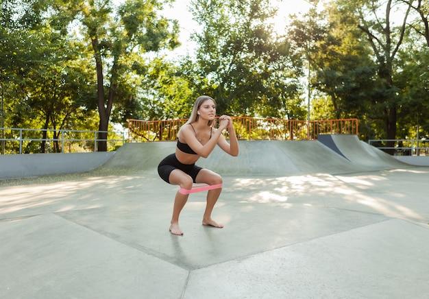 Piękna młoda kobieta sprawny robi poranne ćwiczenia z fitness gumki na zewnątrz.