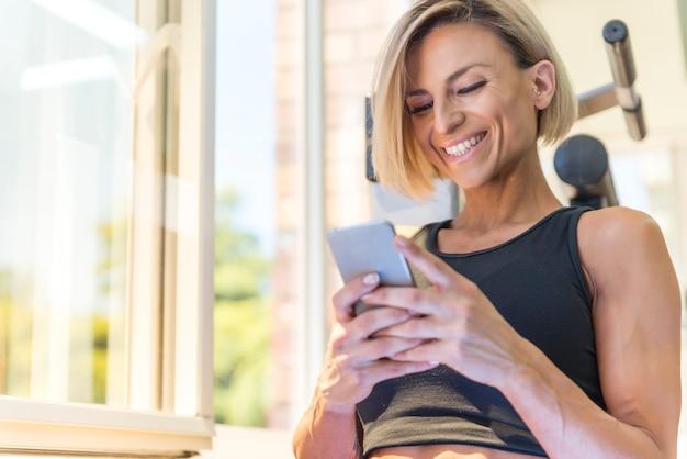 Piękna młoda kobieta sprawny za pomocą smartfona na siłowni. ona ma tatuaże