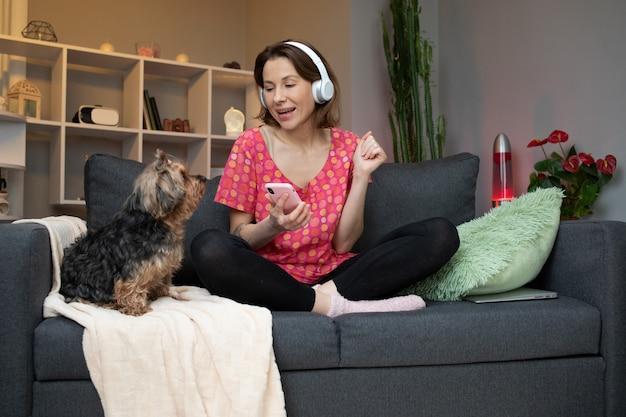 Piękna młoda kobieta, stawiając na słuchawki i słuchanie muzyki.