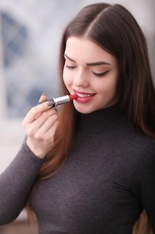 Piękna młoda kobieta stawiając szminkę na ustach