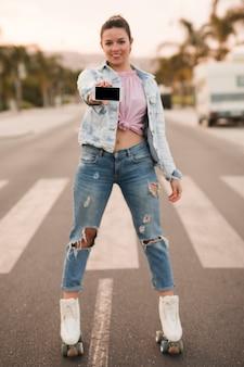 Piękna młoda kobieta stoi na rolkach, pokazując telefon komórkowy na drodze