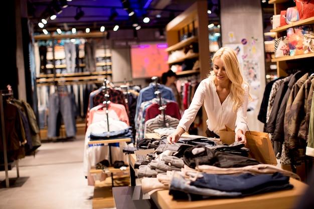 Piękna młoda kobieta stoi przy sklepem odzieżowym z torba na zakupy