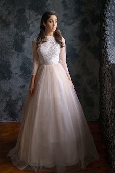Piękna młoda kobieta stoi w delikatnej sukni ślubnej na ciemnej ścianie