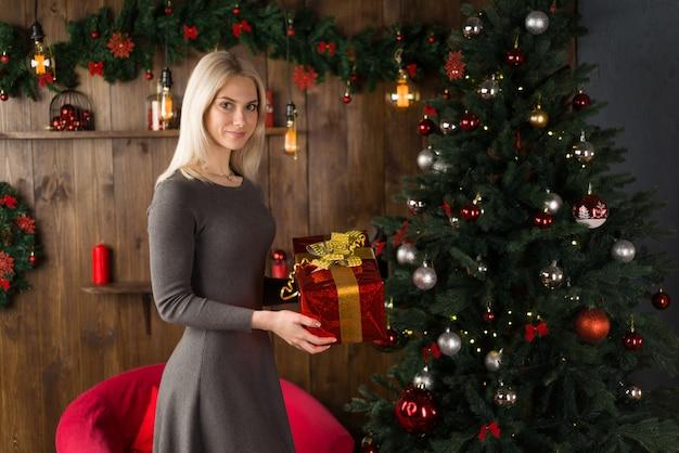Piękna młoda kobieta stoi w pobliżu choinki i trzyma w rękach pudełko na prezent w nowy rok