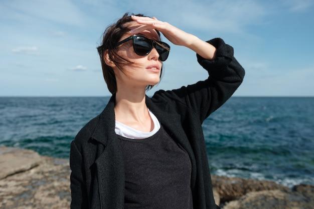 Piękna młoda kobieta stojąc i patrząc daleko na brzegu morza w okularach przeciwsłonecznych