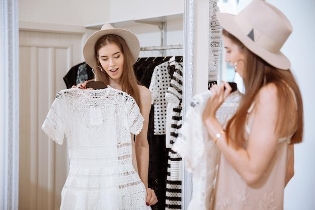 Piękna młoda kobieta stojąc i przymierzając sukienkę przed lustrem