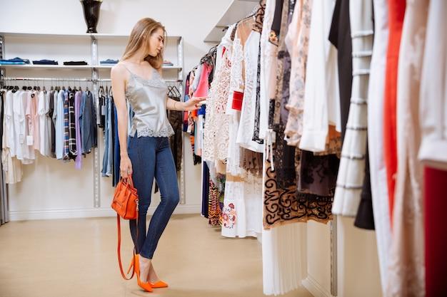 Piękna młoda kobieta stojąc i wybierając ubrania w sklepie odzieżowym