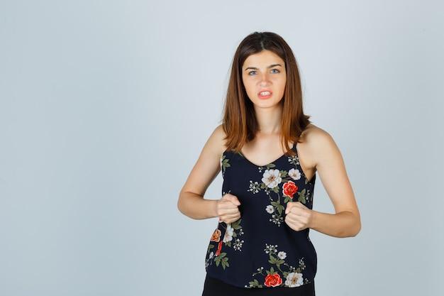 Piękna młoda kobieta stojąc w pozie walki, zaciskając zęby w bluzce i patrząc zły
