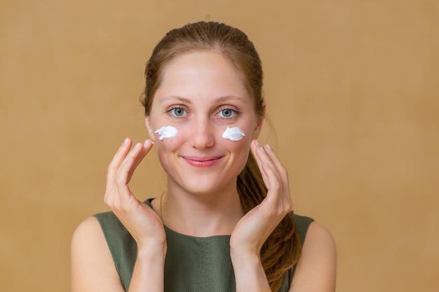 Piękna młoda kobieta stosowania kosmetyków do twarzy w dłoniach