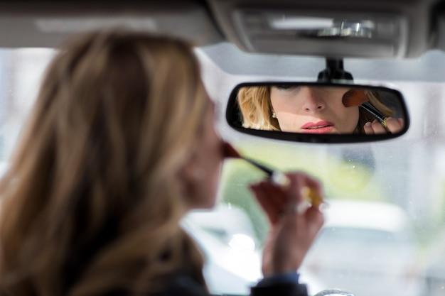 Piękna młoda kobieta stosuje makijaż podczas gdy jadący samochód