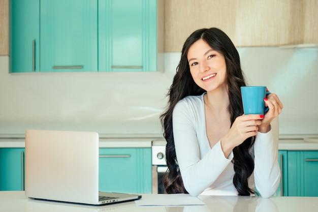 Piękna młoda kobieta studentka (freelancer) w białej sukni i czarnych włosach pracuje w domu z laptopem w kuchni w kolorze turkusowym. w rękach kubka idea szczęścia