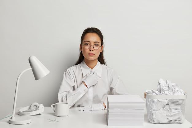 Piękna młoda kobieta studiuje przy biurku