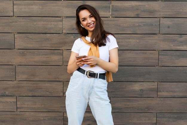 Piękna młoda kobieta szczęśliwa brunet ubrana w ubranie i słuchanie muzyki za pośrednictwem słuchawek bezprzewodowych stojąc na ulicy trzymając i używając telefonu komórkowego patrząc na kamery. miejsce