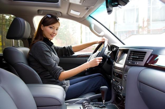 Piękna młoda kobieta szczęśliwa pozowanie wewnątrz nowego samochodu