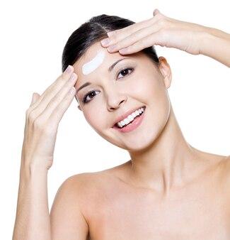 Piękna młoda kobieta szczęśliwa stosując krem kosmetyczny na czole.