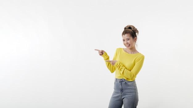 Piękna młoda kobieta szczęśliwa, wskazując na bok