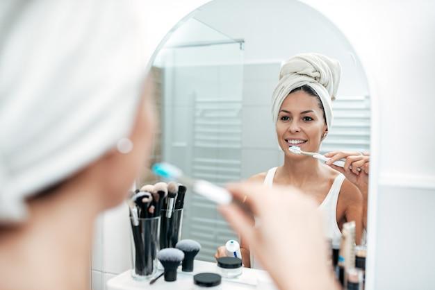Piękna młoda kobieta szczotkuje zęby po prysznic.
