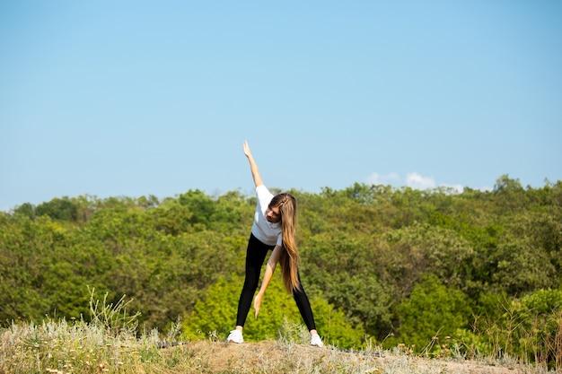 Piękna młoda kobieta szkolenia elastyczność na zewnątrz